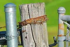 Uma cerca de madeira de deterioração velha chicoteada a uma cerca mais nova do elo de corrente com arame farpado imagem de stock