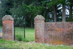 Uma cerca do ferro forjado dá a entrada através de uma cerca velha do tijolo imagem de stock