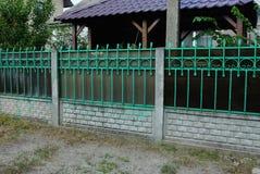Uma cerca longa dos galhos verdes e de tijolos cinzentos imagens de stock royalty free
