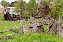 Uma cerca quebrada atrás de que são as sobras de um h de madeira queimado Foto de Stock Royalty Free