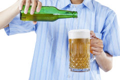 Uma cerveja de derramamento do homem no vidro foto de stock