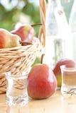Uma cesta com peras e schnapps da pera Fotos de Stock