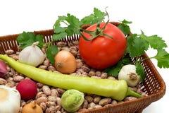 Uma cesta completamente dos feijões, da cebola, do alho com pimentas verdes, dos rabanetes, da couve, do tomate e da salsa isolado Foto de Stock Royalty Free