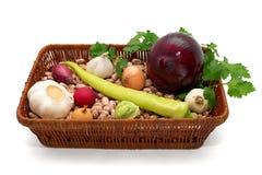 Uma cesta completamente dos feijões, da cebola, do alho com pimentas verdes, dos rabanetes, da couve e da salsa Foto de Stock Royalty Free
