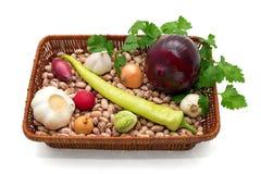 Uma cesta completamente dos feijões, da cebola, do alho com pimentas verdes, dos rabanetes, da couve e da salsa Fotos de Stock