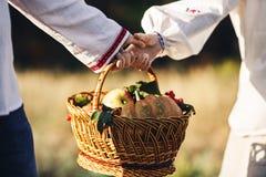 Uma cesta de vime com abóbora, maçãs, e bagas é realizada nas mãos de um indivíduo e de uma menina em camisas bordadas Fotos de Stock Royalty Free