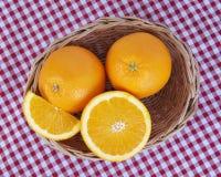 Uma cesta de vime completamente de frutos alaranjados frescos Imagens de Stock Royalty Free