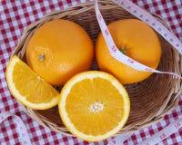 Uma cesta de vime completamente de frutos alaranjados frescos com centímetro Imagens de Stock