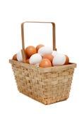 Uma cesta dos ovos brancos e marrons no branco Foto de Stock