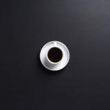 Uma chávena de café branca em um fundo cinzento escuro da mesa Foto de Stock