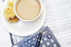 Uma chávena de café e uma calculadora fotografia de stock