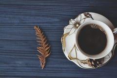 Uma chávena de café na mesa de madeira Escuro - madeira azul Humor da manhã foto de stock royalty free