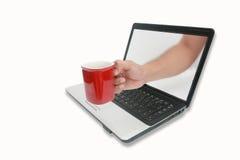 Uma chávena de café vermelha através do computador Foto de Stock