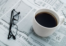 Uma chávena de café, vidros e um jornal Imagens de Stock Royalty Free