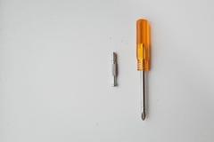 Uma chave de fenda pequena e o parafuso Fotos de Stock Royalty Free