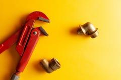 Uma chave de macaco no fundo amarelo com alguns conectores apropriados Para o projeto e a decoração imagem de stock