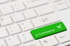 Uma chave verde com texto do comércio eletrónico no teclado branco do portátil Fotografia de Stock Royalty Free