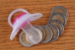 Uma chupeta e moedas em uma tabela fotografia de stock