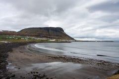 Uma cidade de pesca pequena na costa no pé da montanha foto de stock royalty free