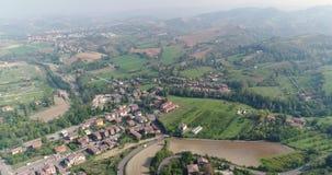 Uma cidade pequena em um vale entre montes verdes, uma vista de cima de, uma casa perto de uma cidade pequena, uma casa em um mon vídeos de arquivo