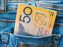 Uma cole??o de c?dulas australianas D?lares no cal?as de brim bolso, close up Algumas contas de cem d?lares colam para fora imagens de stock royalty free