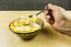 Uma colher com os flocos de milho com o leite e a banana tomados de uma bacia Fotografia de Stock