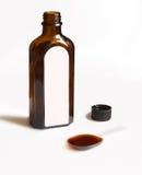 Uma colher com xarope medicinal e o tubo de ensaio de vidro marrom Fotografia de Stock Royalty Free