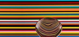 Uma colher contra um fundo colorido, mostrando a reflexão de Imagens de Stock