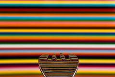 Uma colher contra um fundo muito colorido, com o fundo Fotografia de Stock Royalty Free