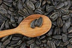 Uma colher de madeira marrom com sementes pretas encontra-se em um montão Fotos de Stock Royalty Free