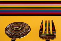 Uma colher e uma forquilha contra um fundo muito colorido, com o b Fotografia de Stock Royalty Free