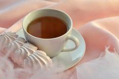 Uma composição clara e pairosa com um copo do chá e de um bolo apetitoso do marshmallow Fotografia de Stock