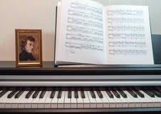 Uma composição da partitura e do teclado de piano Elementos do interior da sala de aula da música Foto de Stock