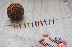 Uma composição de pregadores de roupa de madeira multi-coloridos em uma corda e uma bola de ramos de árvore Foto de Stock