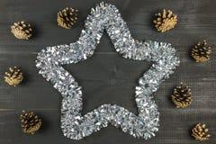 Uma composição do Natal Estrela e cones de Tisnel no fundo de madeira preto fotos de stock