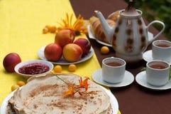 Uma composição exterior com copos de chá, um potenciômetro do chá, uma placa das panquecas, pastelaria, fruto maduro e campo flor Foto de Stock