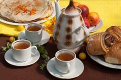 Uma composição exterior com copos de chá, um potenciômetro do chá, uma placa das panquecas, pastelaria, fruto maduro e campo flor Fotografia de Stock Royalty Free