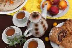 Uma composição exterior com copos de chá, um potenciômetro do chá, uma placa das panquecas, pastelaria, fruto maduro e campo flor Imagens de Stock Royalty Free