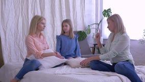 Uma comunicação alegre com a mamã, mãe feliz com filhas bonitas fala e tem o divertimento na cama da família em casa