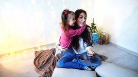 Uma comunicação da irmã fêmea mais idosa com a menina a mais nova que senta-se no assoalho na sala no fundo da parede com a festã video estoque