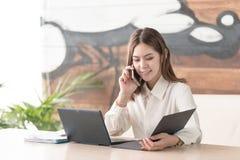Uma comunicação da mulher de negócio que fala no telefone celular Fotos de Stock