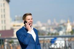 Uma comunicação de sorriso feliz do smartphone do uso do homem de negócios, fundo da skyline O homem no homem de negócios do tern Fotos de Stock Royalty Free