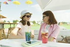 Uma comunicação do pai e do adolescente Assento de fala do adolescente da mãe e da filha no café da rua do verão imagem de stock