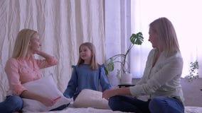 Uma comunicação, a mamã e as filhas da família passam o tempo junto na cama em casa video estoque