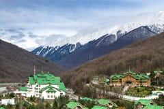 Uma comunidade moderna da casa de campo com uma casa com os telhados verdes situados entre as montanhas fotos de stock