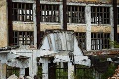 Uma construção arruinada de uma planta com uma fileira de janelas vazias Fotos de Stock Royalty Free