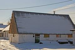 Uma construção velha com uma neve vil do telhado foto de stock