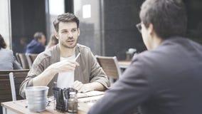 Uma conversação entre dois amigos no café fora fotografia de stock royalty free