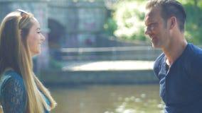 Uma conversa dos pares no beira-rio - têm diferenças pequenas, mas podem facilmente encontrar um acordo vídeos de arquivo