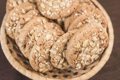 Uma cookie caseiro deliciosa com cereais e sementes encontra-se em uma cesta de vime Fotografia de Stock Royalty Free